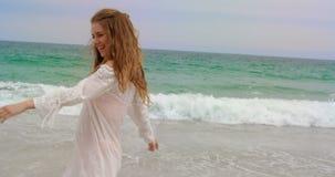 Gelukkige Kaukasische vrouw die bij strand op een zonnige dag 4k dansen stock footage