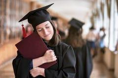 Gelukkige Kaukasische vrouw op haar graduatiedag bij Universiteit stock afbeeldingen