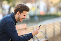 Gelukkige kerel die een slimme telefoon in een park met behulp van Stock Afbeeldingen