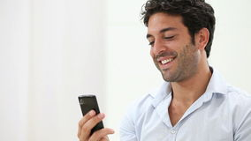 Gelukkige kerel die met slimme telefoon babbelen stock footage