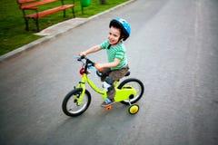 Gelukkige kind berijdende fiets stock afbeelding