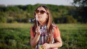 Gelukkige kind blazende zeepbels in de lentepark Langzame Motie stock video