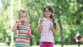 Gelukkige kind blazende zeepbels in de lentepark Twee meisjes hebben pret in het de zomerpark Langzame Motie stock footage