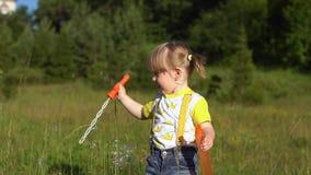 Gelukkige kind blazende zeepbels in de zomerpark Langzame Motie stock footage