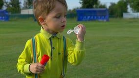 Gelukkige kind blazende zeepbels in een de lentepark Langzame Motie stock videobeelden