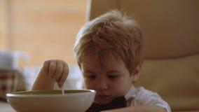 Gelukkige kind het letten op beeldverhalen en het eten van havermoutpap het vrolijke kind eet voedsel zelf met een lepel stock videobeelden