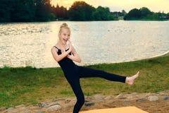 Gelukkige kind het praktizeren yoga pilates op de rivierbank stock foto