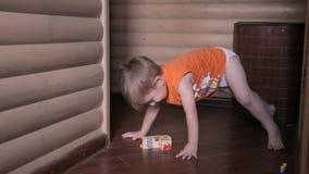 Gelukkige kind het spelen kubussen Hij draagt oranje T-shirt, heeft de ruimte houten muren stock footage