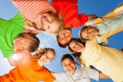 Gelukkige kinderen dicht in cirkel op hemelachtergrond Royalty-vrije Stock Foto's