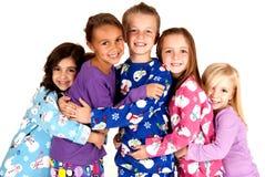 Gelukkige kinderen die in de winterpyjama's elkaar koesteren Royalty-vrije Stock Foto's