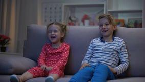 Gelukkige kinderen die de zittings op bank letten van de komediefilm, die pret hebben, die samen lachen stock video