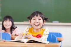 Gelukkige kinderen die in een klaslokaal bestuderen Stock Afbeeldingen