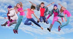 Gelukkige kinderen die en in de blauwe hemel uitoefenen springen Stock Afbeelding