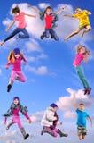 Gelukkige kinderen die en in de blauwe hemel uitoefenen springen Royalty-vrije Stock Foto