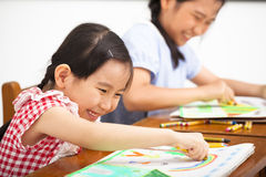 Gelukkige kinderen die in het klaslokaal trekken Stock Fotografie