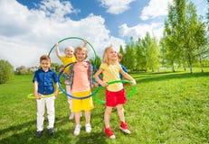 Gelukkige kinderen die hulahoepels houden tijdens oefeningen royalty-vrije stock afbeelding