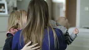 Gelukkige kinderen die hun moeder in de slaapkamer koesteren stock video