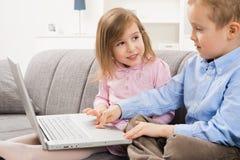 Gelukkige kinderen die laptop computer met behulp van royalty-vrije stock afbeelding