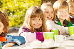Gelukkige kinderen die met theekoppen buiten zitten Royalty-vrije Stock Foto