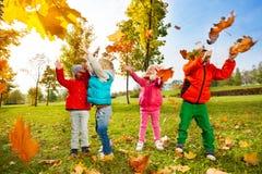 Gelukkige kinderen die met vliegende bladeren in park spelen royalty-vrije stock foto's