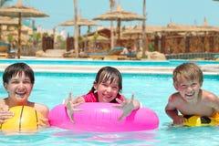 Gelukkige kinderen die in pool spelen Stock Afbeeldingen