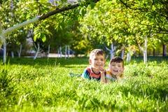 Gelukkige kinderen die pret hebben in openlucht Jonge geitjes die in de zomerpark spelen Weinig jongen en zijn broer die op groen royalty-vrije stock foto's