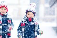 Gelukkige kinderen die pret met sneeuw in de winter hebben royalty-vrije stock afbeelding