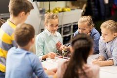 Gelukkige kinderen die robots bouwen op roboticaschool stock foto's