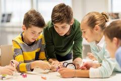 Gelukkige kinderen die robots bouwen op roboticaschool stock foto