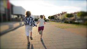 Gelukkige kinderen die samen het houden van handen op de weg in werking stellen De stralen van de zon glanzen in hun gezichten stock footage