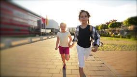 Gelukkige kinderen die samen het houden van handen op de weg in werking stellen De stralen van de zon glanzen in hun gezichten stock video
