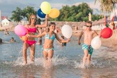 Gelukkige kinderen die samen met ballons het water doornemen stock afbeelding