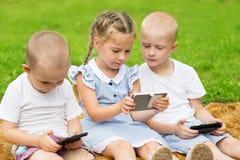 Gelukkige kinderen die smartphones zitting op het gras gebruiken Stock Foto