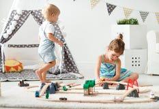 Gelukkige kinderen die in speelgoed thuis in speelkamer spelen royalty-vrije stock afbeeldingen