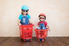 Gelukkige kinderen die stuk speelgoed auto thuis drijven royalty-vrije stock afbeeldingen
