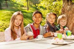 Gelukkige kinderen die thee met cupcakes drinken Stock Foto's