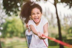 Gelukkige kinderen die touwtrekwedstrijd spelen bij het park stock foto