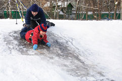 Gelukkige kinderen die van een weinig sneeuwheuvel glijden Royalty-vrije Stock Foto