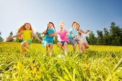 Gelukkige kinderen die voetbal in gele weide spelen royalty-vrije stock foto
