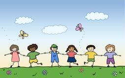 Gelukkige kinderen die voor handen op gebied houden Stock Foto's