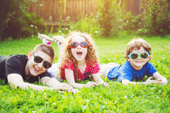 Gelukkige kinderen in glazen die op het gras liggen Gelukkige familieconce royalty-vrije stock afbeelding