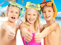 Gelukkige kinderen met duim-omhooggaand gebaar bij strand Royalty-vrije Stock Foto