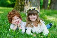 Gelukkige kinderen op het gras Royalty-vrije Stock Afbeeldingen