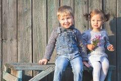 Gelukkige kinderen openlucht bij dalingsseizoen, die bij bank zitten Eerste D Royalty-vrije Stock Afbeelding