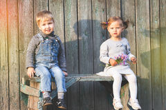 Gelukkige kinderen openlucht bij dalingsseizoen, het zitten bank Eerste datum Royalty-vrije Stock Fotografie
