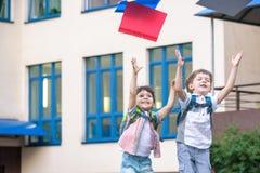Gelukkige kinderen - twee jongensvrienden met boeken en rugzakken op Th royalty-vrije stock fotografie