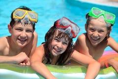 Gelukkige kinderen in zwembad stock foto's