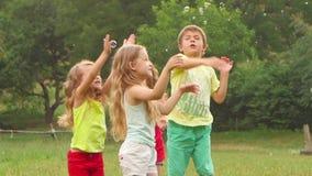 Gelukkige kinderenjongen en drie meisjes die vangstzeepbels op een de zomergazon spelen Langzame Motie stock videobeelden