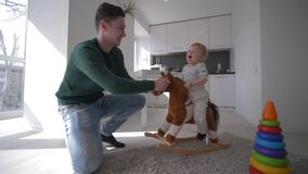 Gelukkige kinderjaren, het jonge papa spelen met aardige zuigelingsjongen op pluche paardenplaatsing en het slingeren thuis in ke stock videobeelden