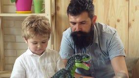 Gelukkige kinderjaren Huis Dino Park Zoon en vaderspel tijdens de Juraperiode Een stuk speelgoed dinosaurus voor de familie, het  stock footage